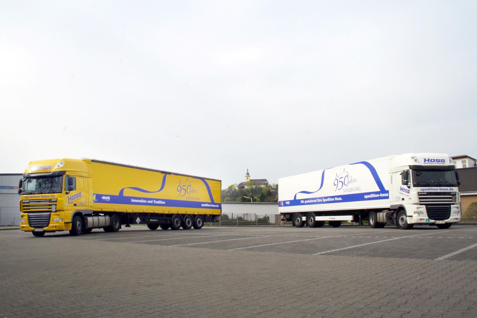 Das Bild zeigt zwei LKWs mit Anhänger der Spedition Hoss GmbH & Co. KG