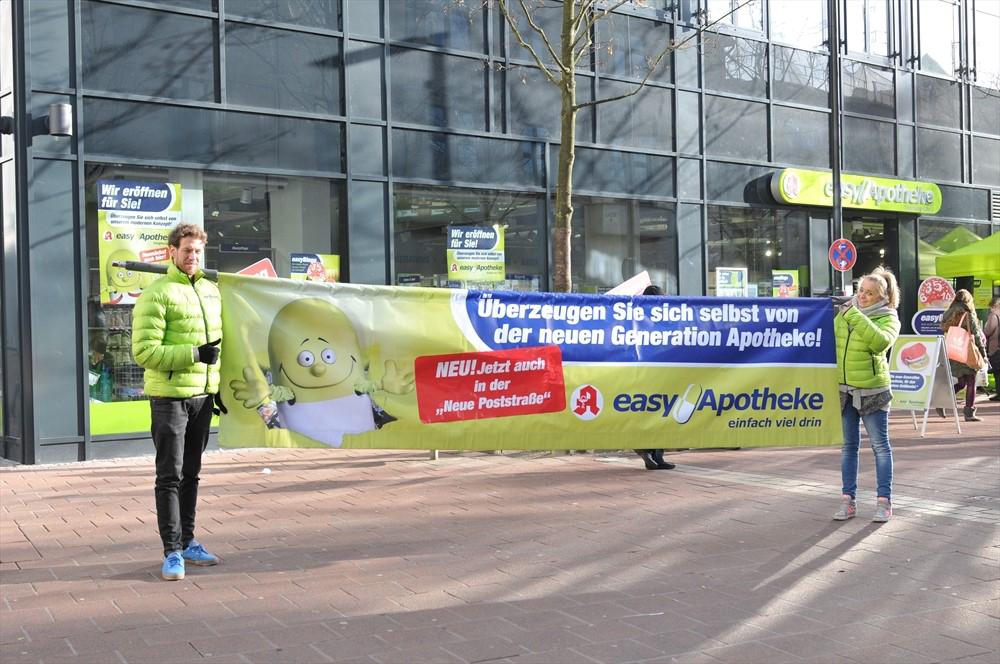 Das Bild zeigt 2 Mitarbeiter der easyApotheke Siegburg City die einen Werbebanner der Apotheke aufspannen