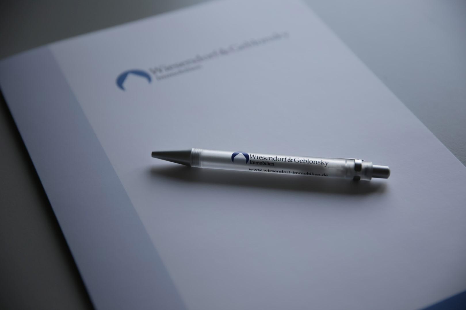 Das Bild zeigt einen Schreibblock mit dem Logo von Wiesendorf & Geblonsky Immobilien GbR auf dem ein Kugelschreiber liegt