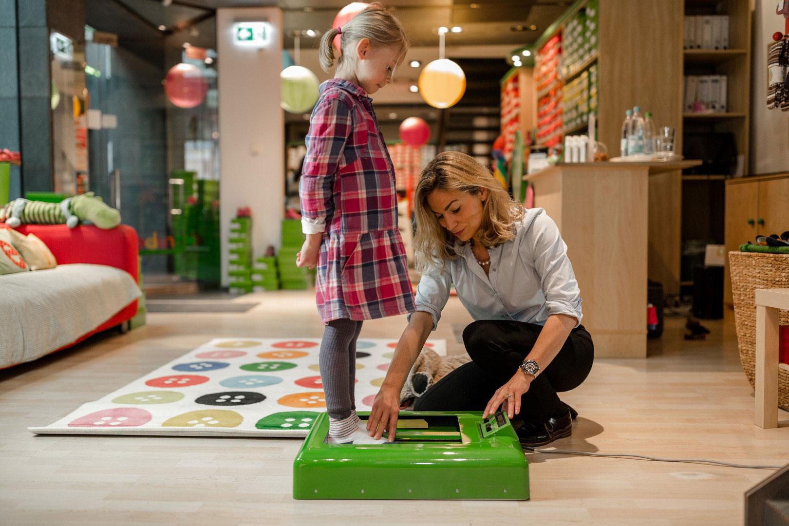 Auf den Bild ist zu sehen, wie die Füße eines Kindes vermessen werden