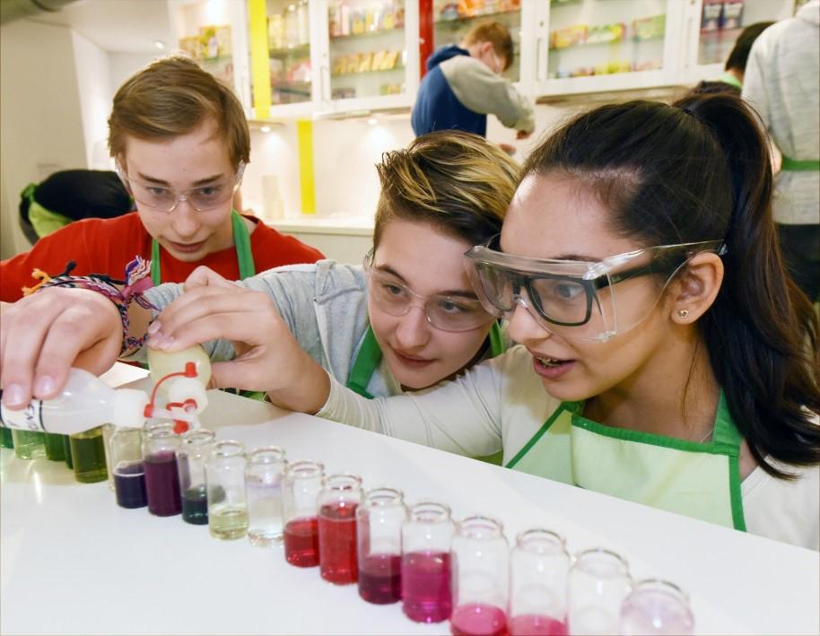 Auf dem Bild sind Kinder abgebildet,die ein Experiment durchführen