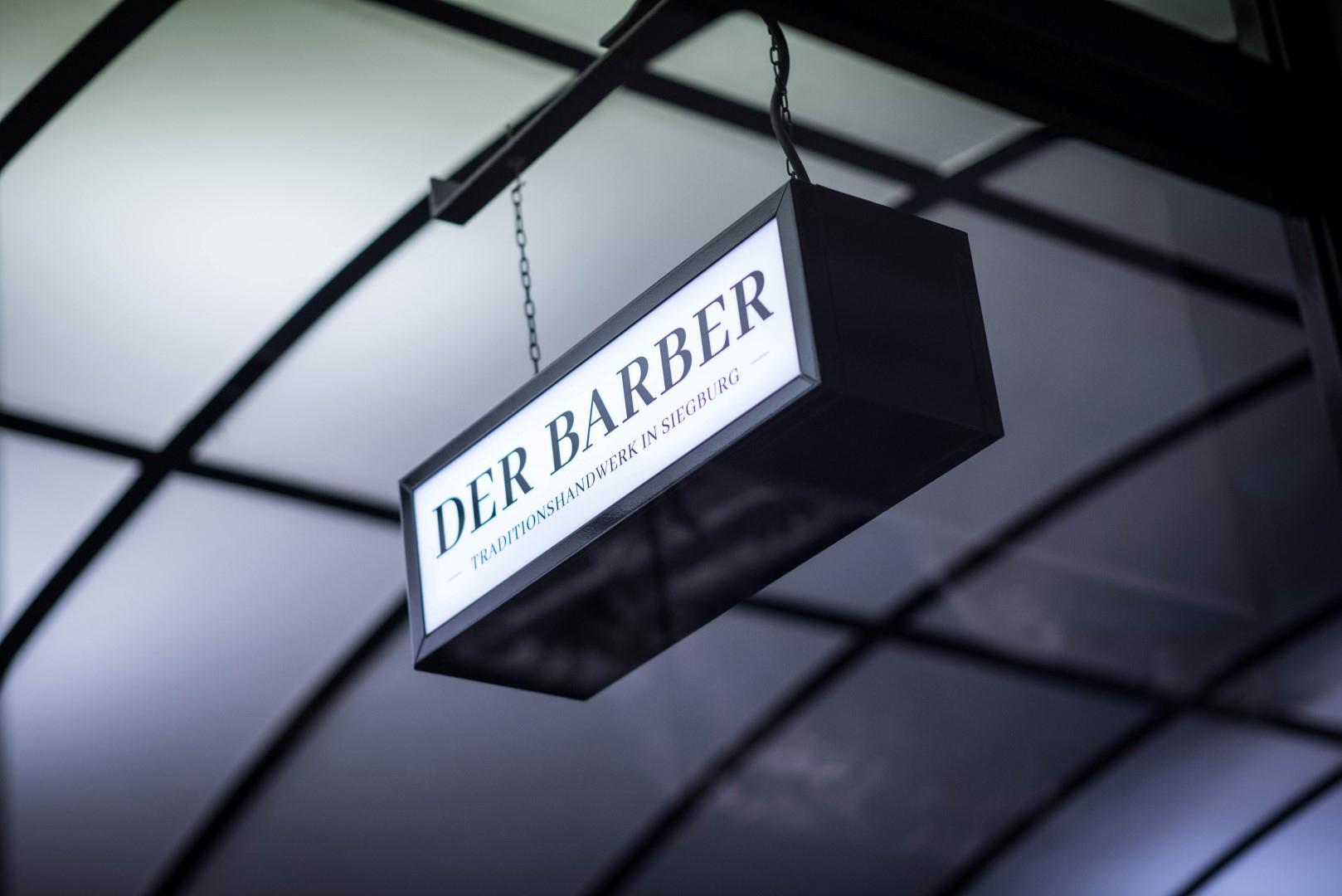 Das Bild zeigt ein Eingangsschild mit der Aufschrift des Barbershops