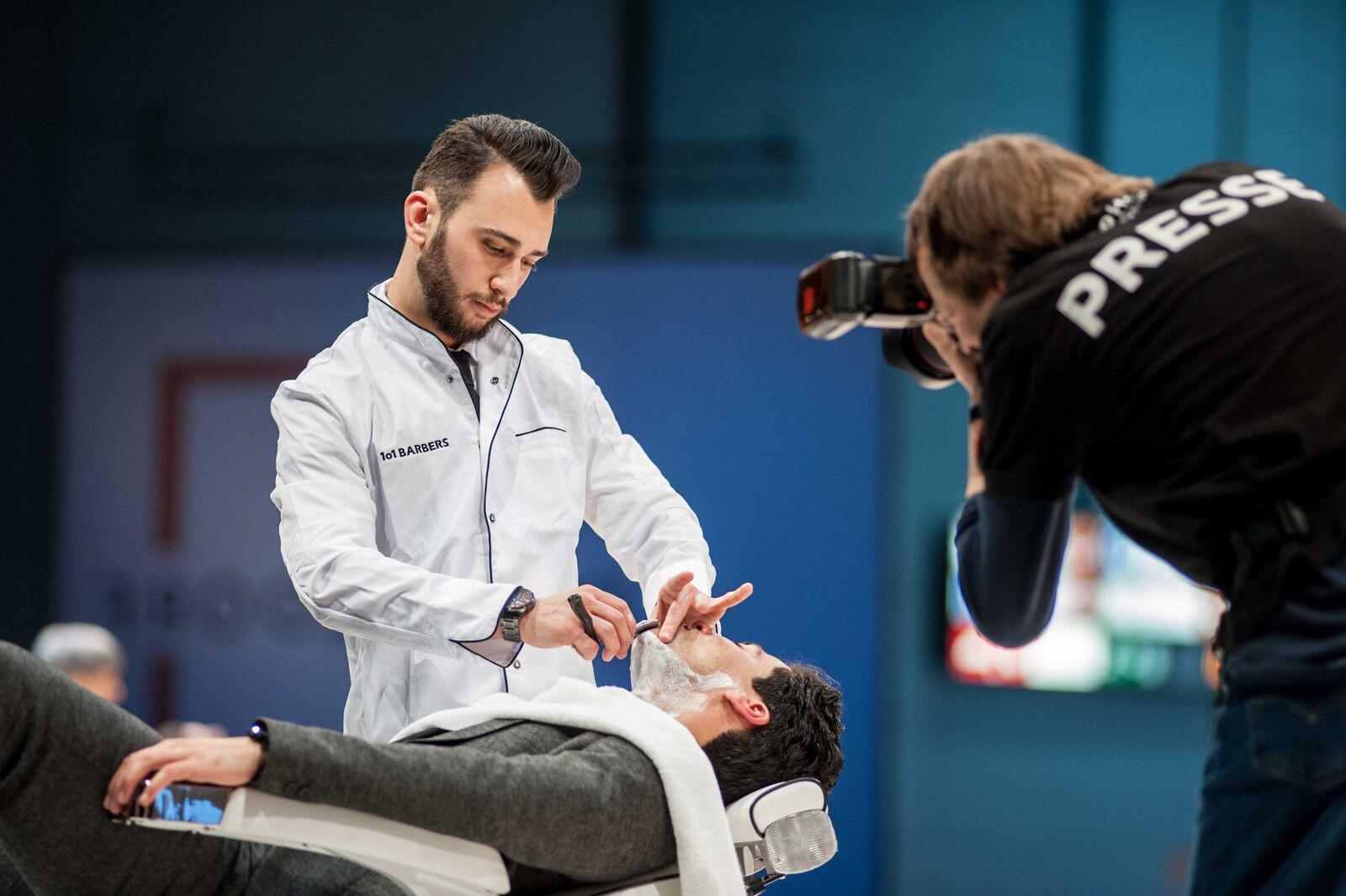 Das Bild zeigt einen Barber bei der Arbeit. Ein Fotograf von der Presse macht ein Foto davon.