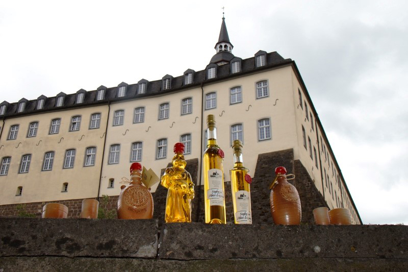 Das Bild zeigt mehrere Liqueur-Flaschen der Abtei-Liqueur Siegburg GmbH vor der Siegburg Abtei auf dem Michaelsberg