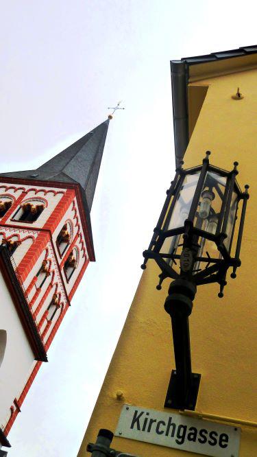 Das Bild zeigt ein Straßenschild mit der Aufschrift Kirchgasse an einem gelben Gebäude in Siegburg
