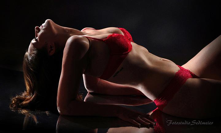 Das Bild zeigt das Foto einer Frau in roten Dessous