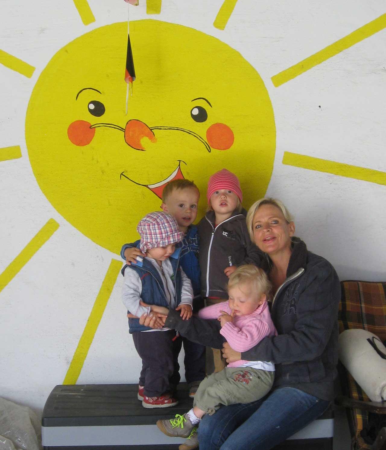 Das Bild zeigt die Pflegekraft von der Tagespflege Sonnenschein zusammen mit 4 Kindern vor einer Wand, auf der eine Sonne gemalt ist