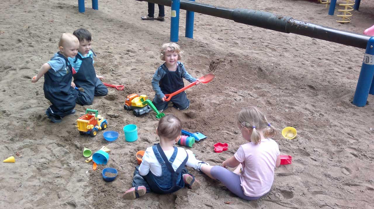 Das Bild zeigt spielende Kinder in einem Sandkasten