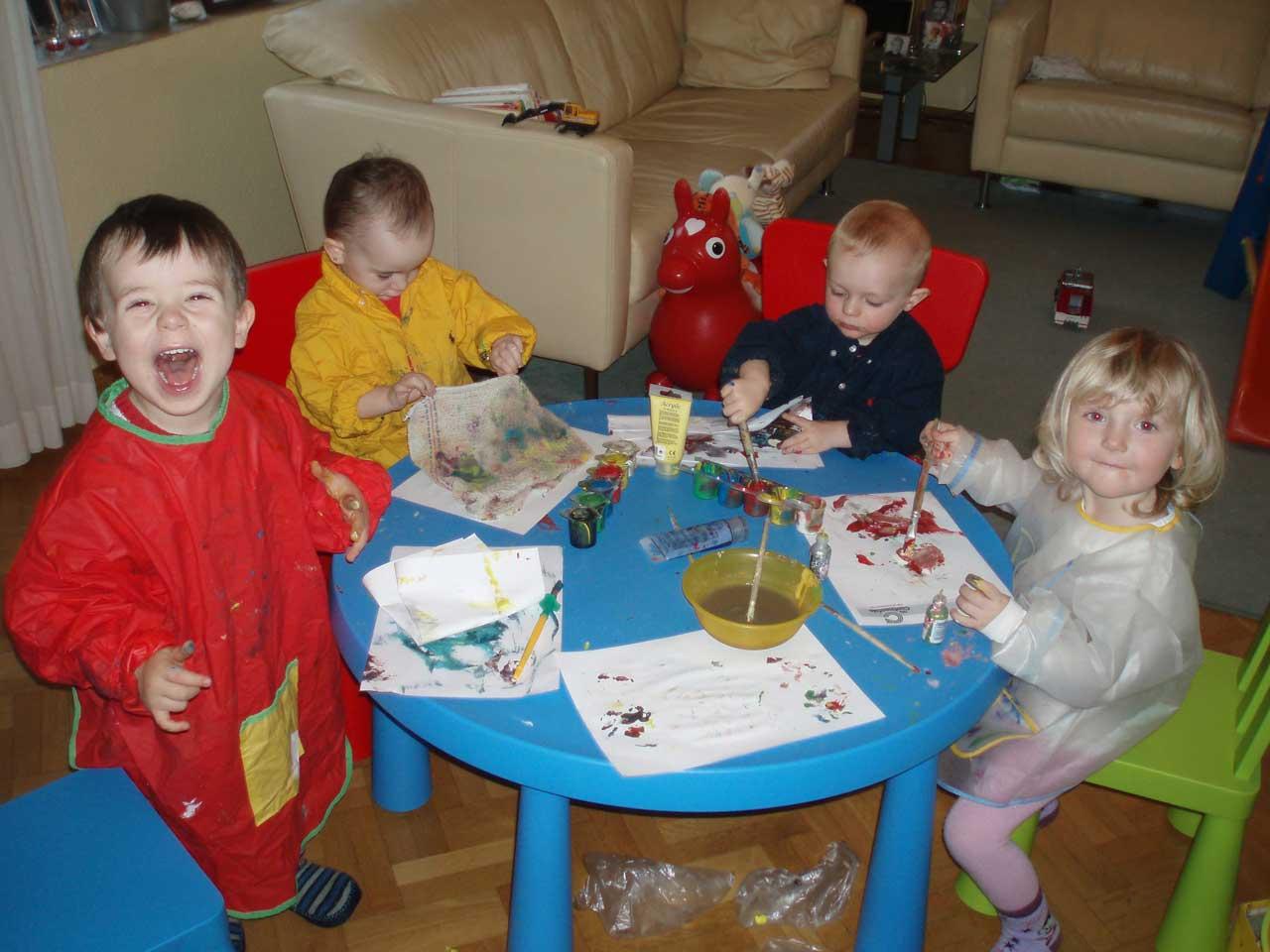 Das Bild zeigt Kinder, die gemeinsam an einen blauen Tisch malen