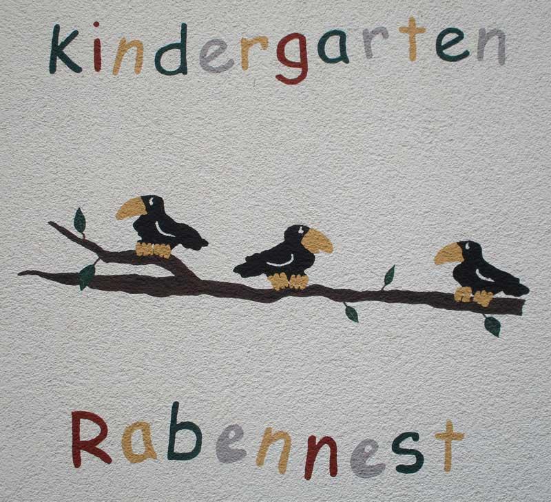 Das Bild zeigt das Logo der Kindertagesstätte Rabennest auf der Fassade des Kita-Gebäudes. Das Logo zeigt 3 Vögel sitzend auf einem Ast.