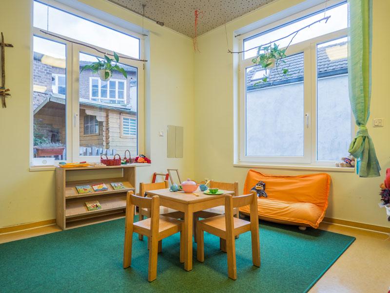Das Bild zeigt 1 Holztisch zusammen mit 4 Holzstühlen auf einen grünen Teppich und wurde in den Räumlichkeiten der Kindertagesstätte Rabennest aufgenommen