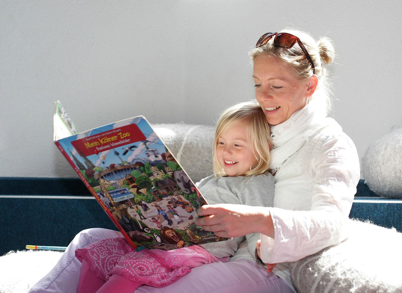 Auf dem Bild ist eine Mutter mit ihrer Tochter zu sehen, die in einem Kinderbich lesen