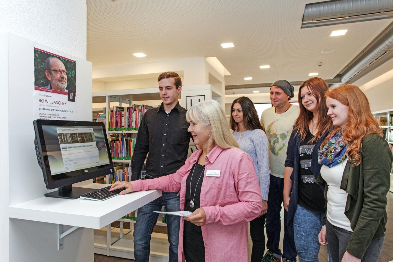Das Bild zeigt eine Gruppe von Besuchern vor einem Katalog-PC