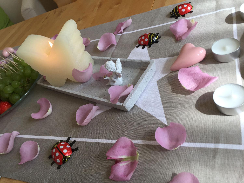 Das Bild zeigt einen, mit Teelichtern und Blüttenblättern, geschmückten Tisch