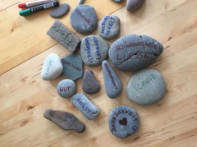Auf dem Bild sind beschriftete Steine auf einer Tischplatte zusehen