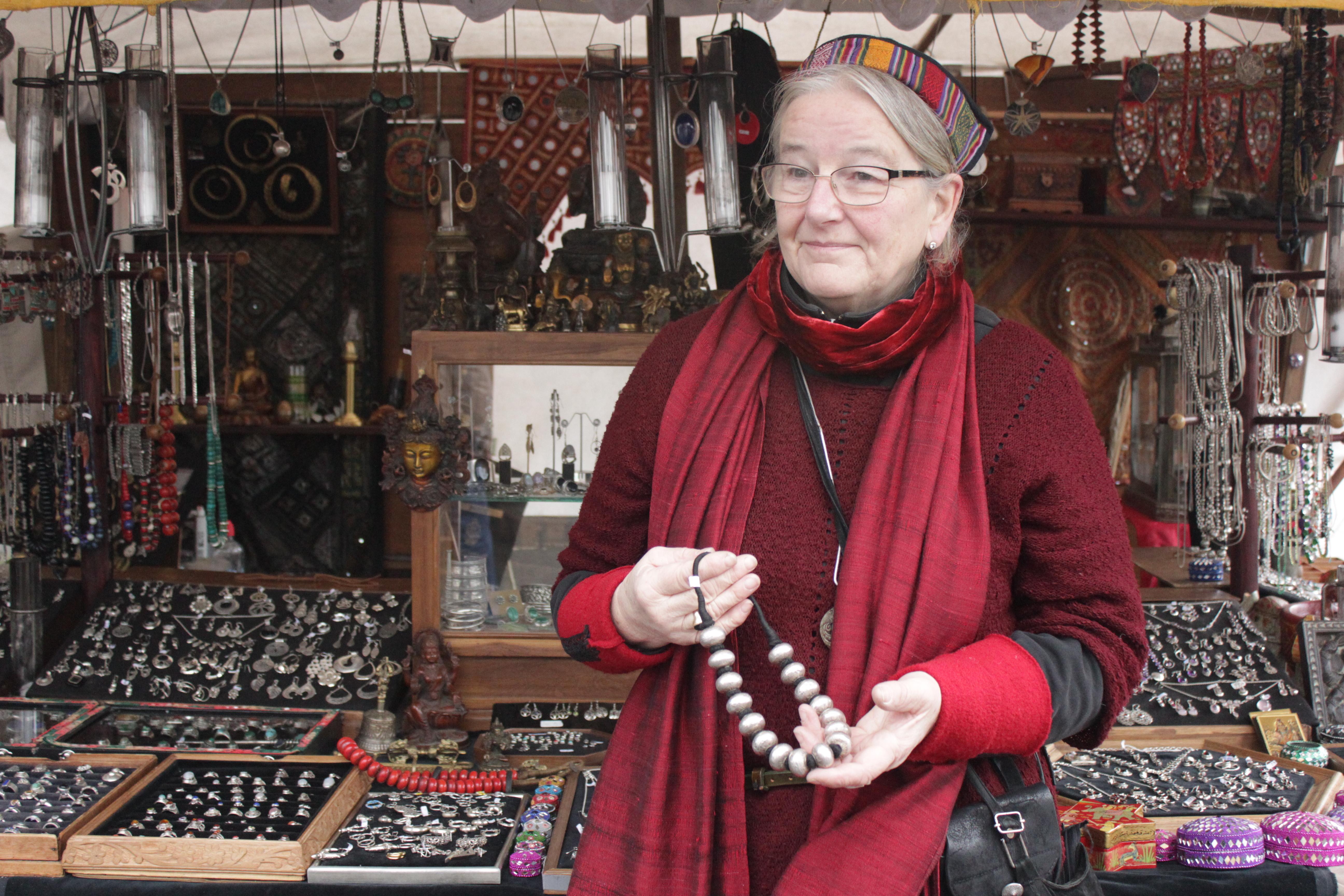 Schmuckhändlerin zeigt eine selbstgemachte Kette vor Ihrem Stand
