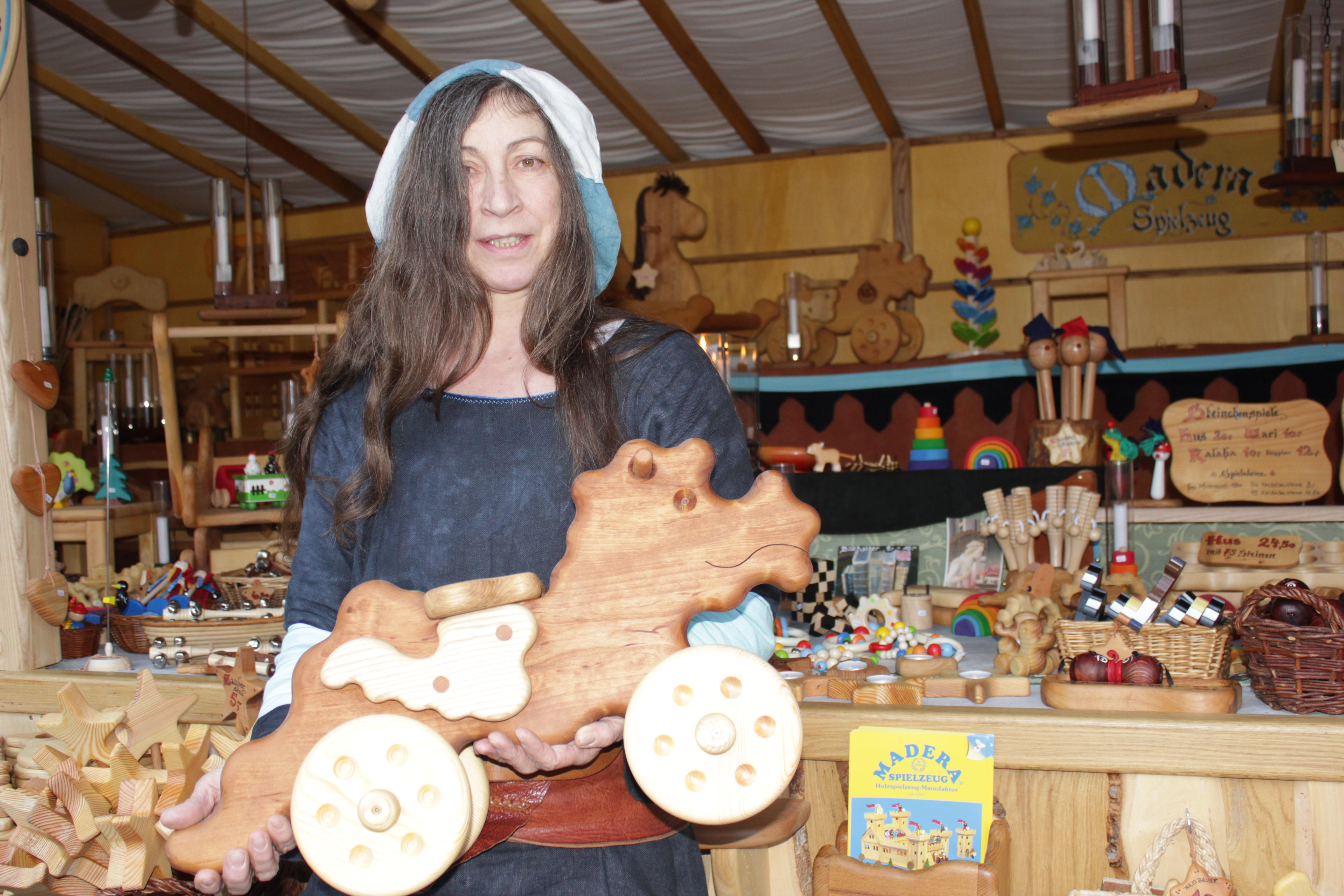 Verkäuferin zeigt Holzdrachenlaufrad vor dem Madera Stand
