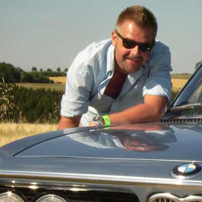 Das Bild zeigt eine Person, die sich auf der Motorhaube eines Oldtimers abstützt