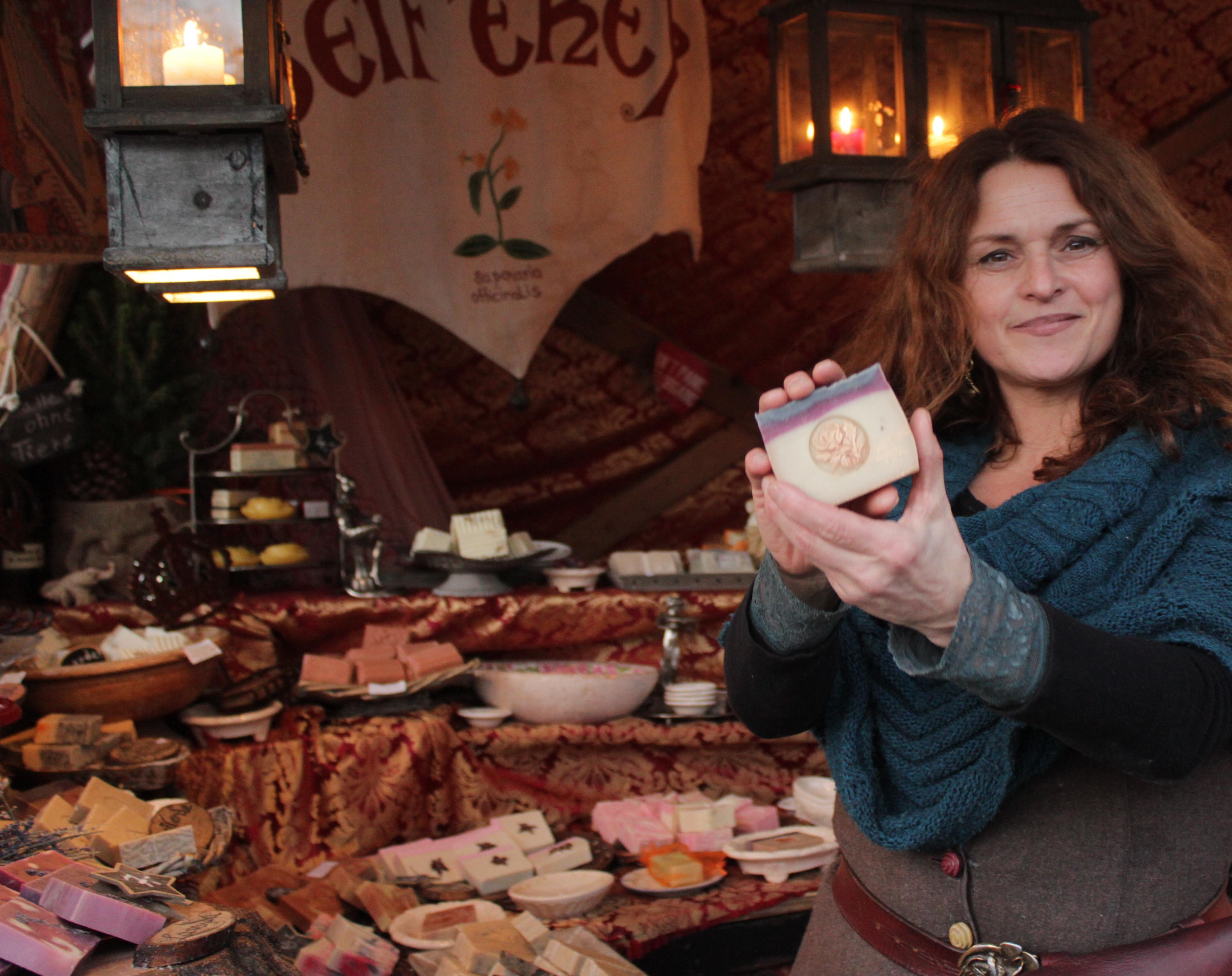 Die Verkäuferin, Daniela Exner-Groß, hält einer Ihrer selbstgemachten veganen Seifen vor ihrem Stand der Seiferey.