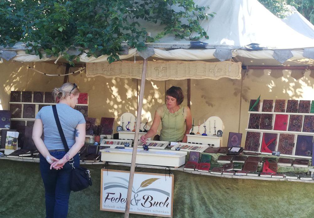 """Die Verkäuferin, Gesine Aufdermauer, steht in ihrem Stand """"Feder & Buch"""", welcher in Leder gebundene Bücher, sowie Schreibfedern aus Glas."""
