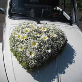 Das Bild zeigt ein Blumengesteck auf einem Hochzeitsauto