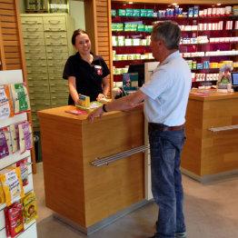Das Bild zeigt eine Apothekerin sowie einen Kunden bei einem Beratungsgespräch in der Siegburger Adler Apotheke