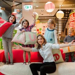 Auf den Bild stehen Kinder auf einer roten Couch und halten Kissen mit den Buchstaben des Firmennamens in der Hand. Davor sitzt eine Verkäuferin.
