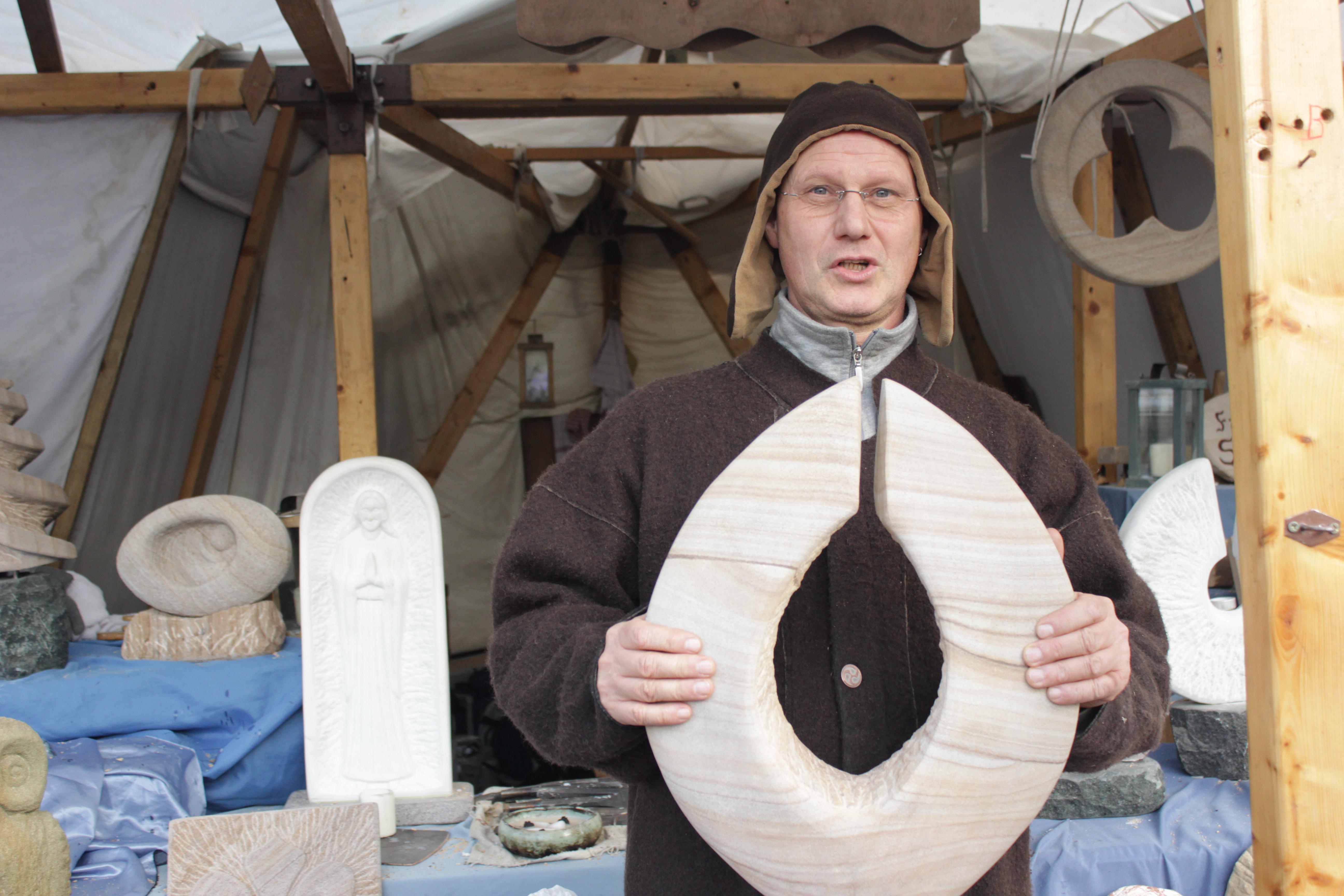 Der Verkäufer, Harald Dahmen, hält einen seiner selbst angefertigten Werkstücke aus Sandstein vor seinem Stand in der Hand.